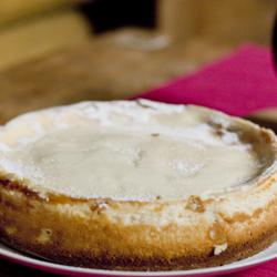 Vaaleapintainen juustokakku, joka kypsennetty ja käännetty valkoiselle ruokalautaselle.