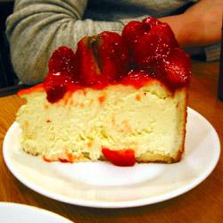 Viipale juustokakkua, jonka päällä runsaasti tuoreita mansikoita ja niiden seassa mansikkahilloa.