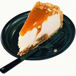 Mustalla lautasella taustasta irti leikattu valokuva karamellisoidusta juustokakkuviipaleesta.