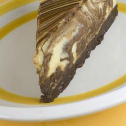 Marmorikuvioitu juustokakkuviipale. Pohjallinen on hyvin tumma ja suklaamainen.